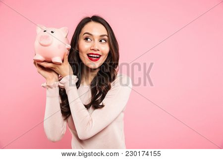 Joyous young woman 20s in casual clothing holding piggybank with lots of money isolated over pink background