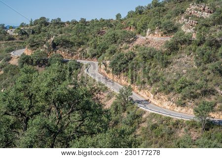 Long View Of Cyclist Group Climbing Mountain With Curved Road