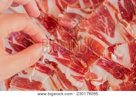 Top View Of Woman Left Hand Picking Serrano Ham Slice, Focus On Top Of Choosen Slice, Shallow Depth