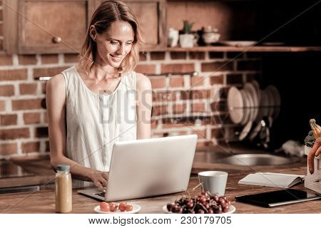 Remote Work. Attractive Cheerful Pleasant Woman Smiling And Looking At The Laptop Screen While Worki