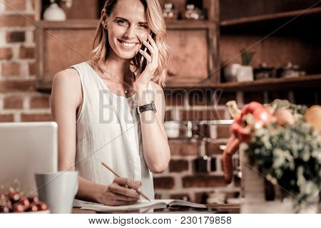 Phone Call. Delighted Positive Cheerful Woman Holing Her Phone And Making A Phone Call While Being R