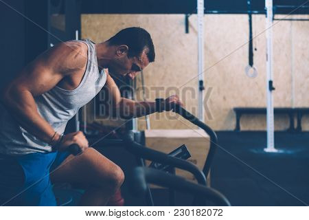 Side View Of A Young Sporty Man Doing Calorie Assault Exercise On A Fitness Routine At The Box Gym