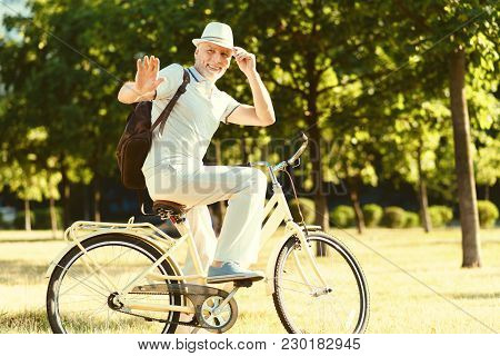 Time To Go. Nice Delighted Aged Man Holding His Hat And Saying Goodbye While Riding His Bike
