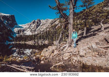 Woman tourist near Dream Lake at autumn in Rocky Mountain National Park. Colorado, USA.