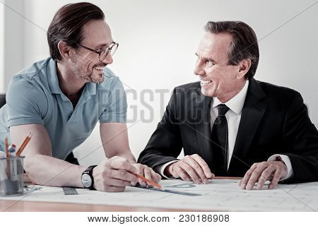 Friendly Atmosphere. Enigmatical Man Wearing Glasses And Keeping Smile On Face While Talking To His