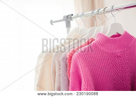 A Hanger With Things. Knitted Sweaters Hang On Hangers. Bright Sweaters. Spring Clothes. Fashion. Co