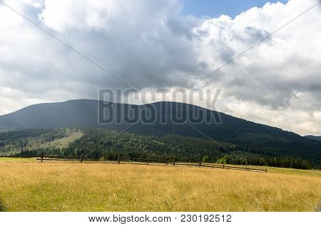 Mountain Landscape With Mountains And Field. Wooden Rural Fence. View Of The Mountains With A Front