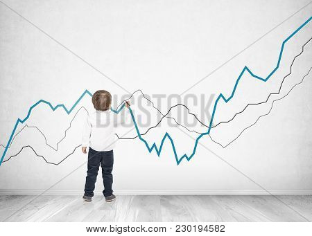 Rear View Of A Cute Little Boy Wearing A White Shirt And Dark Blue Jeans Writing Or Drawing With A M