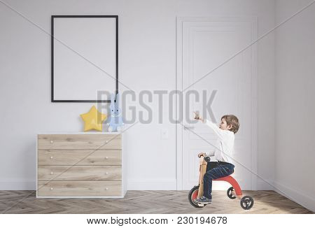 Cute Little Boy In A White Shirt And Dark Blue Jeans Is Riding A Tricycle And Showing With His Finge