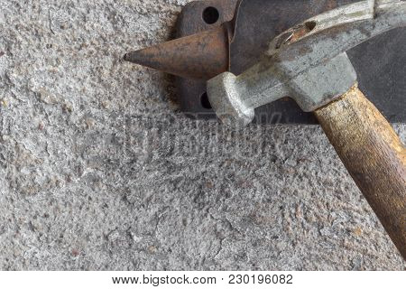 Old Small Hammer And Miniature Anvil With Concrete Background