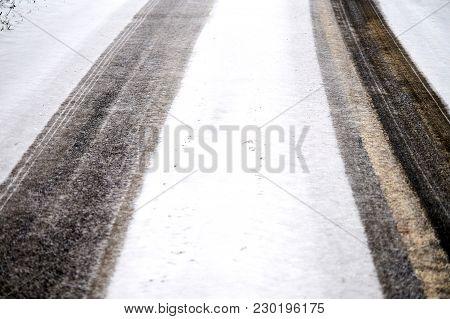 Car Tracks In Snow On Winter Asphalt Road.