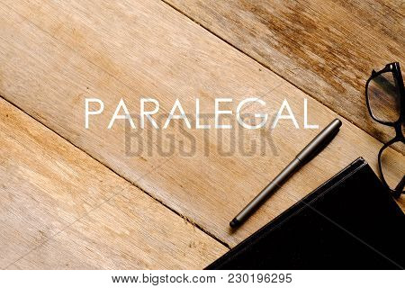 Top View Of Eyeglasses,notebook And Pen On Wooden Background Written With Paralegal.