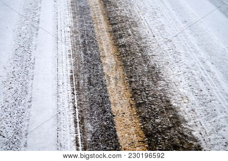 Tracks In Snow On Winter Asphalt Road.