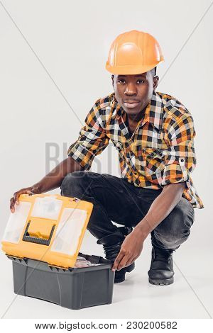 African American Construction Worker In Helmet Takes Out Tools From Yellow Plastic Tool Box