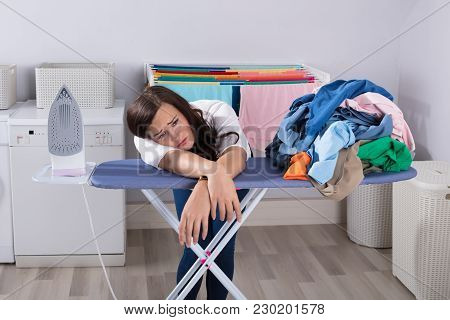 Unhappy Woman Leaning On Ironing Board Next To Piles Of Clothes
