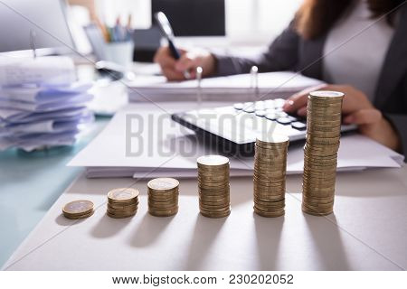 Close-up Of Increasing Stacked Coins In Front Of Businesswoman Calculating Bill