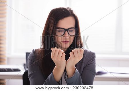 Close-up Of A Young Businesswoman Looking At Her Finger Nails In Office
