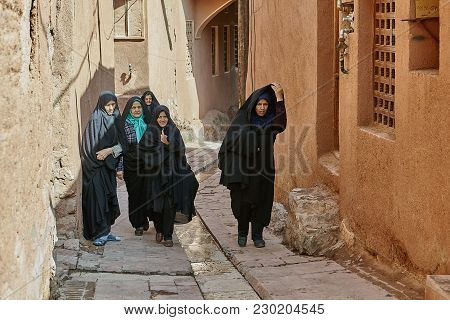 Abyaneh, Iran - April 26, 2017: Group Of Iranian Women In Hijabs Are Walking Along A Narrow Street I