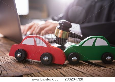 Close-up Of Two Green And Red Wooden Cars On Desk In Courtroom