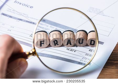 Close-up Of A Human Hand Looking At Fraud Blocks Through Magnifying Glass On Invoice
