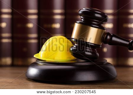 Close-up Of Gavel And Yellow Hard Hat In Courtroom
