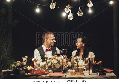 Bride And Groom Kissing With Glass Of Wine In Hands