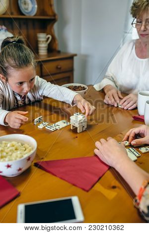 Little Girl Playing Dominoes With Her Mother And Her Grandmother In The Living Room
