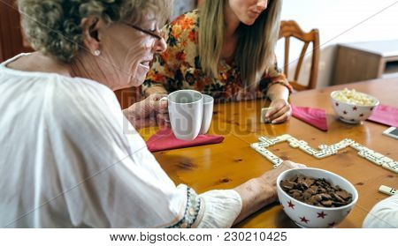 Senior Mother And Daughter Playing Domino In The Living Room