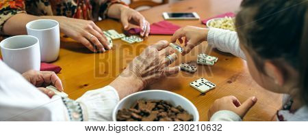 Unrecognizable Grandmother, Daughter And Granddaughter Playing Domino In The Living Room