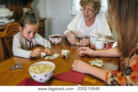 Grandmother, Daughter And Granddaughter Playing With Dominoes In The Living Room