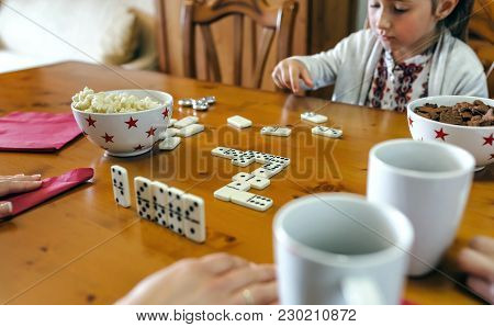 Little Girl Playing Domino With Her Family In The Living Room