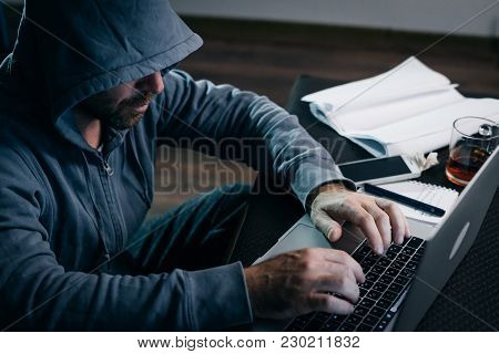 An Experienced Hacker Working On A Laptop At Home