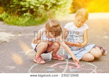 Girls paint hopscotch game with chalk at park
