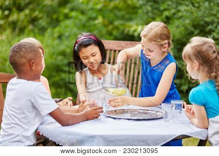 Interracial group of children as friends drink water at party