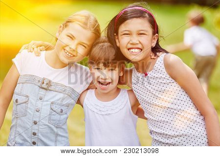 Happy group of girls in kindergarden in summer