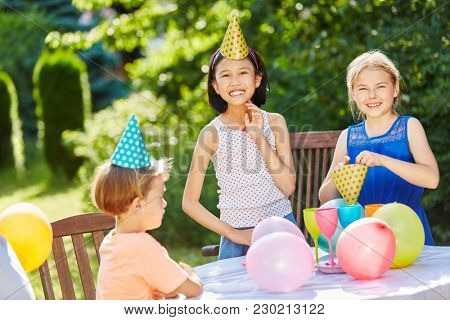 Kids celebrate together at birthday party with balloons in summer in garden