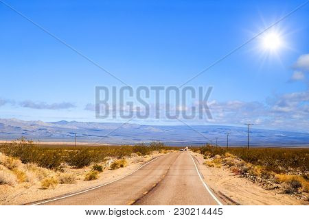 A Long Narrow Stretching Across A Flat Desert Floor With Mountains In The Background In A Spring Tim