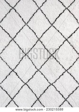 Simple Geometric Design Of A White Rug With Black Lines.
