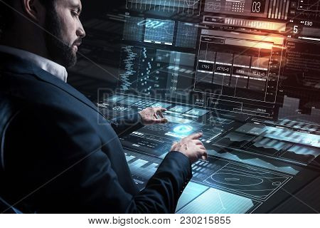 Careful Specialist. Calm Concentrated Young Programmer Carefully Touching A Futuristic Screen While