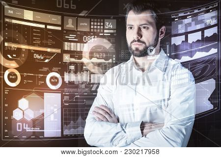 Calm Specialist. Clever Professional Young Programmer Standing With His Arms Crossed And Feeling Con