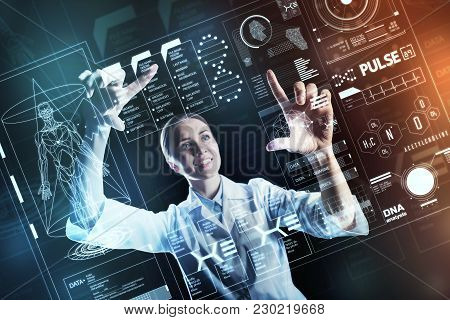 Using Technologies. Clever Experienced Medical Worker Looking Happy While Touching The Futuristic Sc