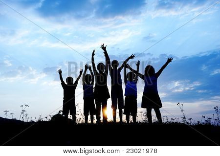 group of happy children playing on meadow, blue sky, summertime