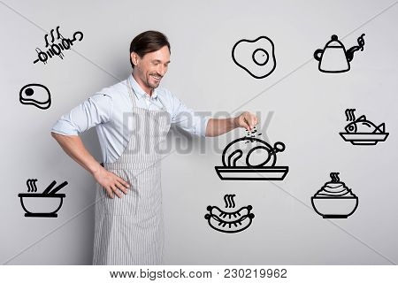 Delicious Meal. Experienced Professional Cook Looking Glad While Standing In His Convenient Kitchen