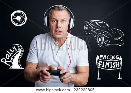 Video Game. Serious Interested Man Feeling Impressed While Standing With A New Game Console In His H
