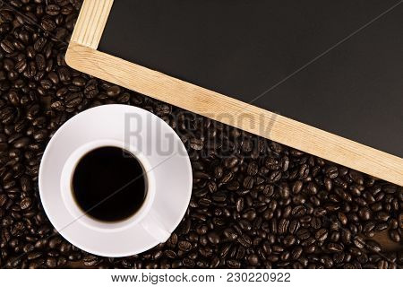 Cup Of Coffee And Coffee Beans On Old Wooden Background, Black Board On Top. Directly Above.