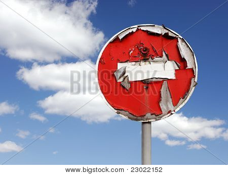 Conceptual stock photo of old red peeled No Entry road sign over blue sky background Restricted area concept Isolated with clipping path