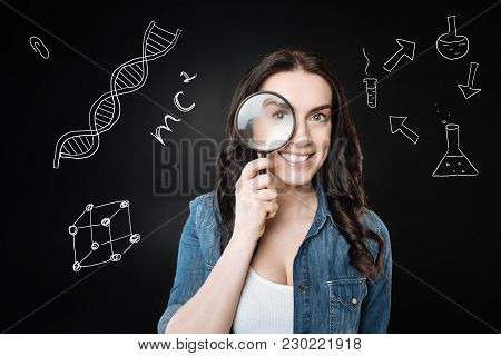 Scientific Research. Positive Clever Emotional Student Smiling And Looking Through The Magnifying Gl