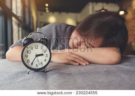 An Asian Woman Taking A Nap On The Table With Black Alarm Clock