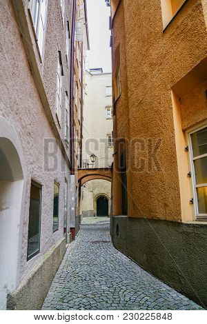 Old Narrow Cobbled Laneway Between Tall Buildings In Old Town Salzburg, Austria.