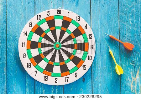 The Darts  On A Blue Wooden Background